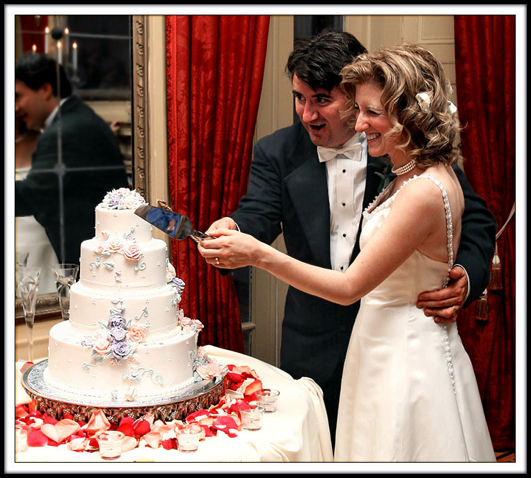 A Bride And Groom Cutting The Wedding Cake