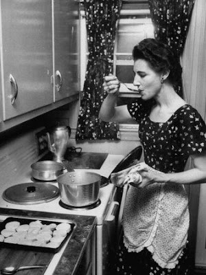 Black and white photograph of woman in vintage kitchen cooking