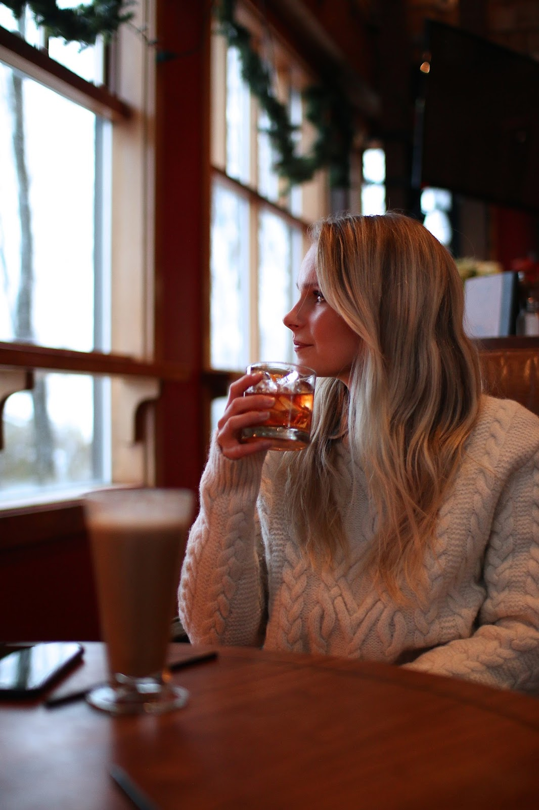 winter cozy in beige cable knit sweater sipping a cozy christmas cocktail