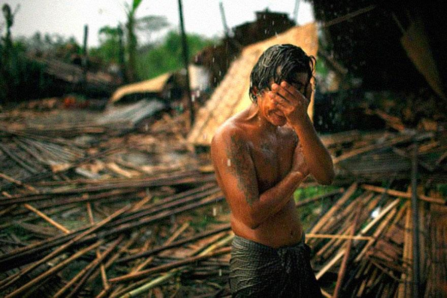 30 of the most powerful images ever - Hhaing The Yu, 29, holds his face in his hand as rain falls on the decimated remains of his home near Myanmar's capital of Yangon (Rangoon). In May 2008, cyclone Nargis struck southern Myanmar, leaving millions homeless and claiming more than 100,000 lives