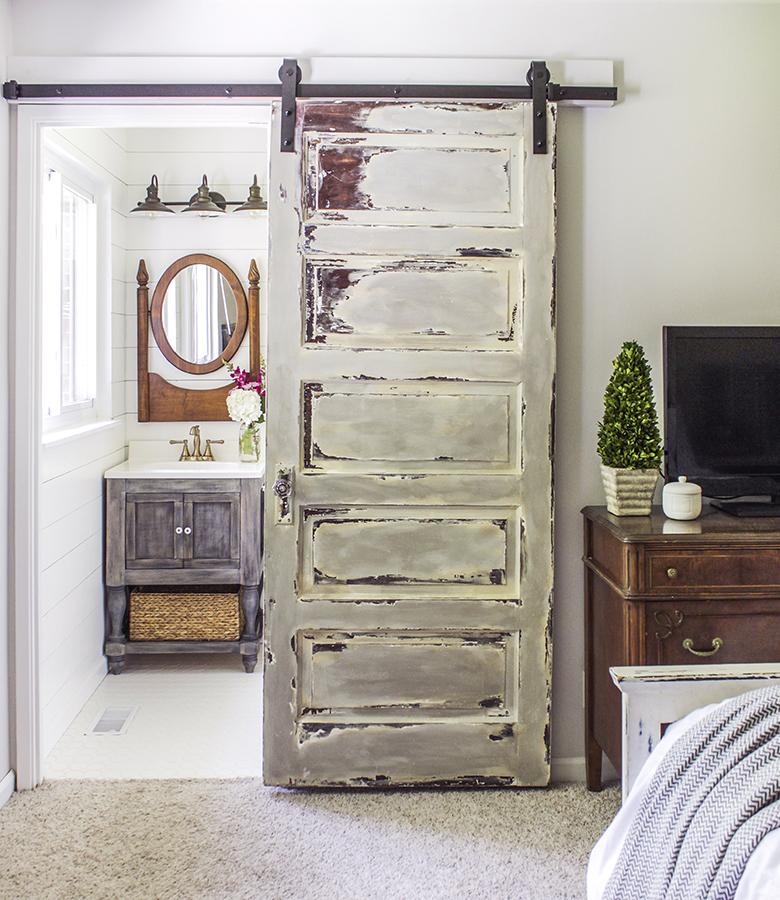five panel vintage door is converted into a sliding barn door for bathroom in master bedroom