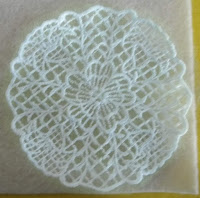 ebroidered lace on tulle, about 4 inches round. sown on cream felt