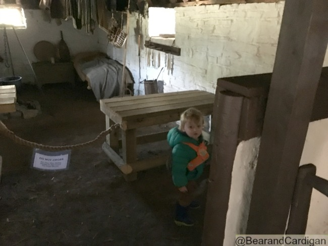 toddler inside a cottage with wooden bed in background