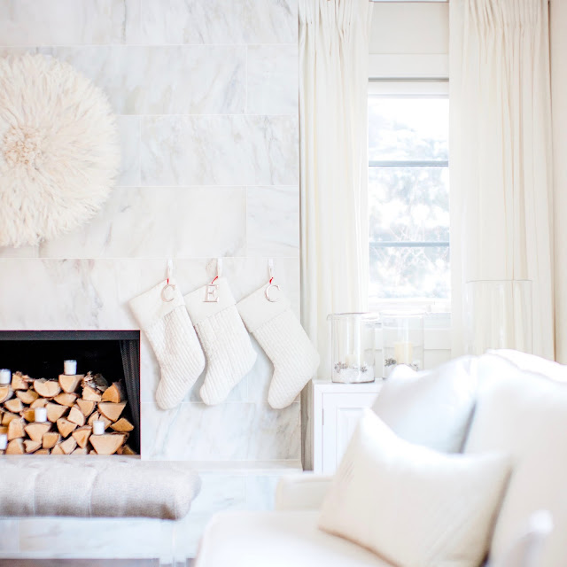 White juju hat on marble fireplace with white velvet pottery barn stockings