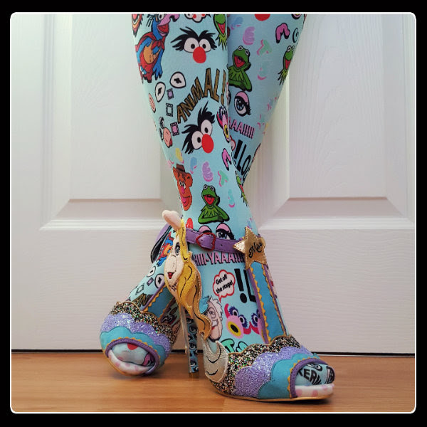 crossed legs wearing Miss Piggy sandals and Disney Muppets Irregular Choice tights