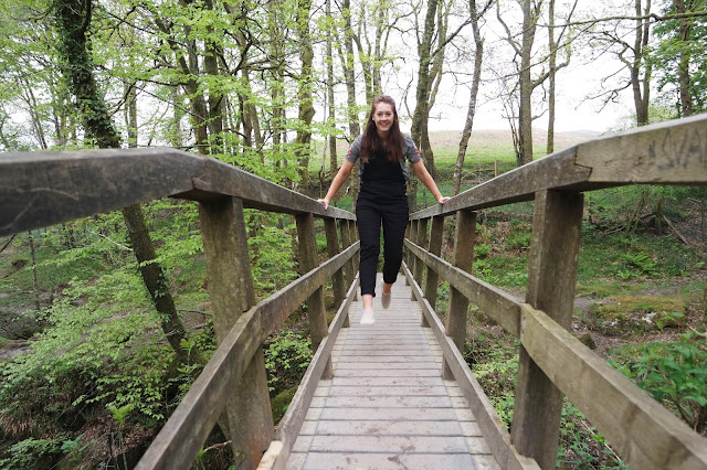 lyd jumping on a wooden bridge, wearing black dungarees