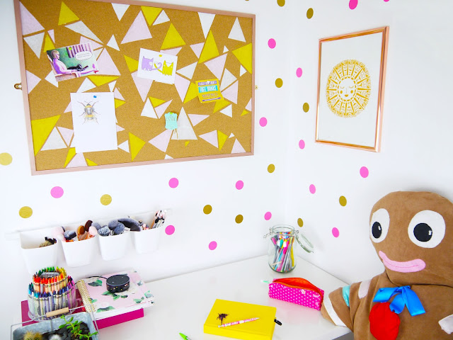 a white room with gold and pink polka dots on the wall, yellow and pink geometric design noticeboard, sun print on the wall, giant gingerbread teddy sat at the desk