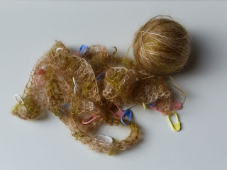 A ball of silk-mohair lace weight yarn and a scarf in progress. Coloured plastic stitch markers can be seen (pink, blue, yellow)