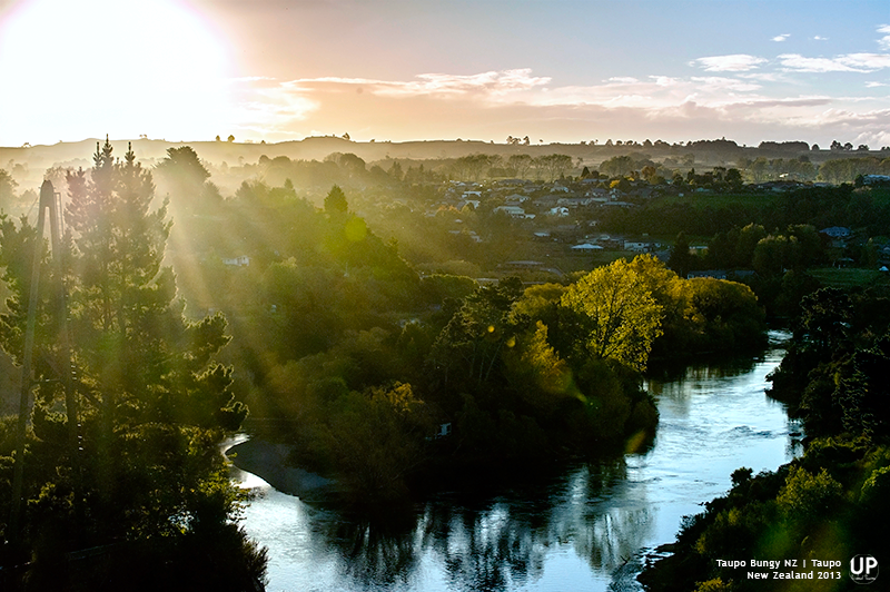 Sunset view from famous Taupo bungy jump site, captured at the perfect moment where the sun angled just above far mountain range, sun ray penetrate through misty ground and show meander of Waikato river flown along