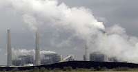 In this March 16, 2011, file photo, exhaust rises from smokestacks in front of piles of coal in Thompsons, Texas. A federal appeals court on Tuesday ordered the Environmental Protection Agency to relax some limits it set on smokestack emissions that cross state lines and taint downwind areas with air pollution from power plants they can't control. (Photo Credit: AP/David J. Phillip, File) Click to Enlarge