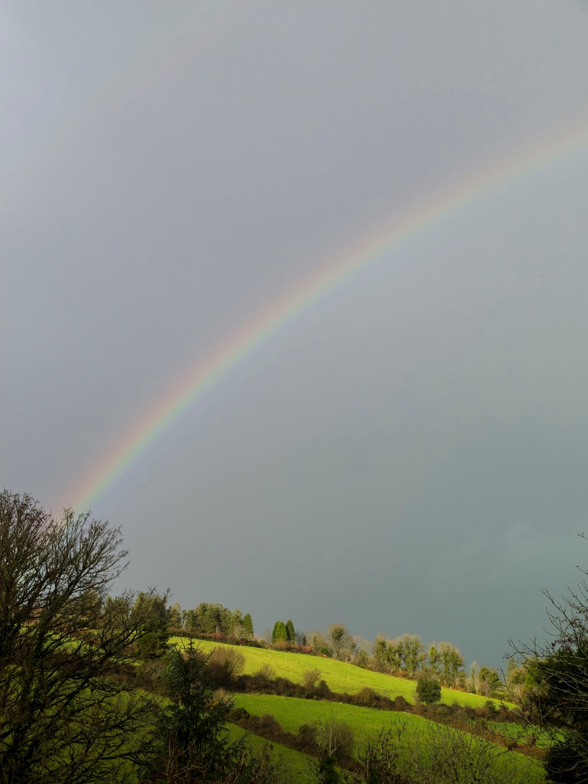Rainbow on a grey sky and sun shining on the top of a hill.