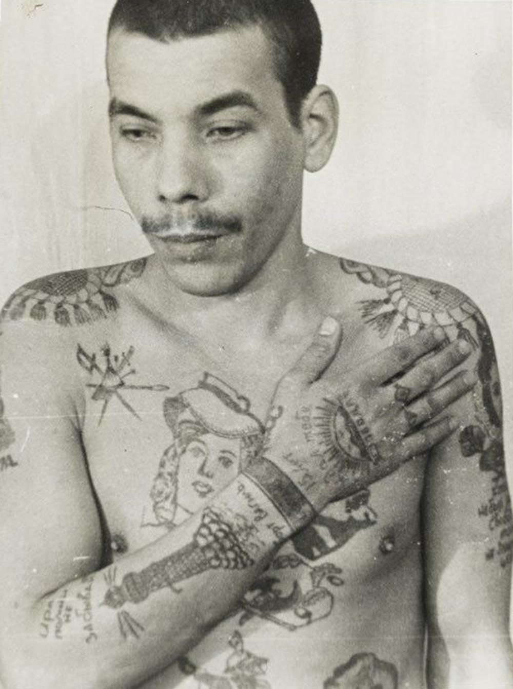 This man is a Muslim; his features also indicate he is not Russian. Text on the arm reads 'Remember me, don't forget me' and 'I waited 15 years for you.' On his stomach (left) is a religious building with a crescent moon. He is not an authoritative thief, but has tried to imitate them with his tattoos to increase his standing within the prison. The lighthouse on his right arm denotes a pursuit of freedom. Each wrist manacle indicates a sentence of more than five years in prison.