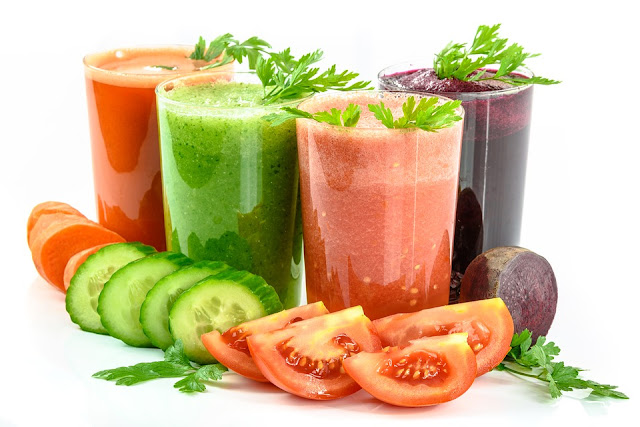 vegetable juices in tall glasses - carrot juice, cucumber and mint juice, tomato juice and beetroot juice