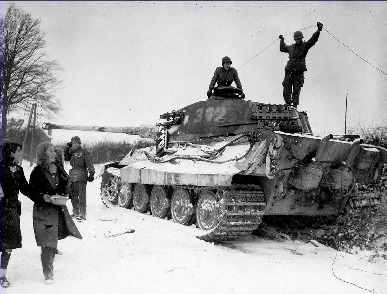 two american soldiers inspect a destroyed german king tiger tank belgium 1944