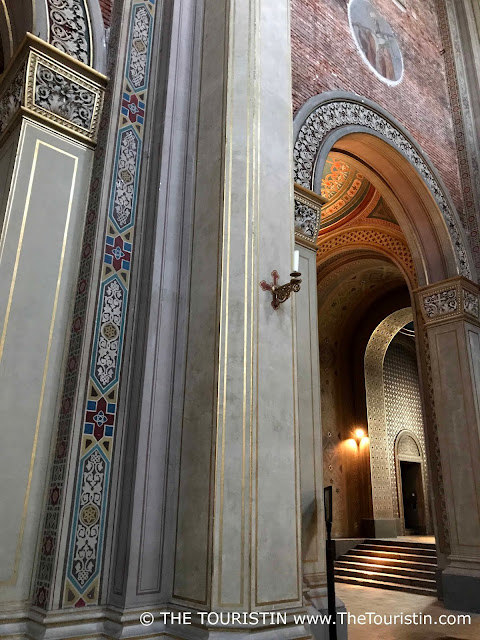 Blue, red, gold, green coulred vaulted doorways in a church.