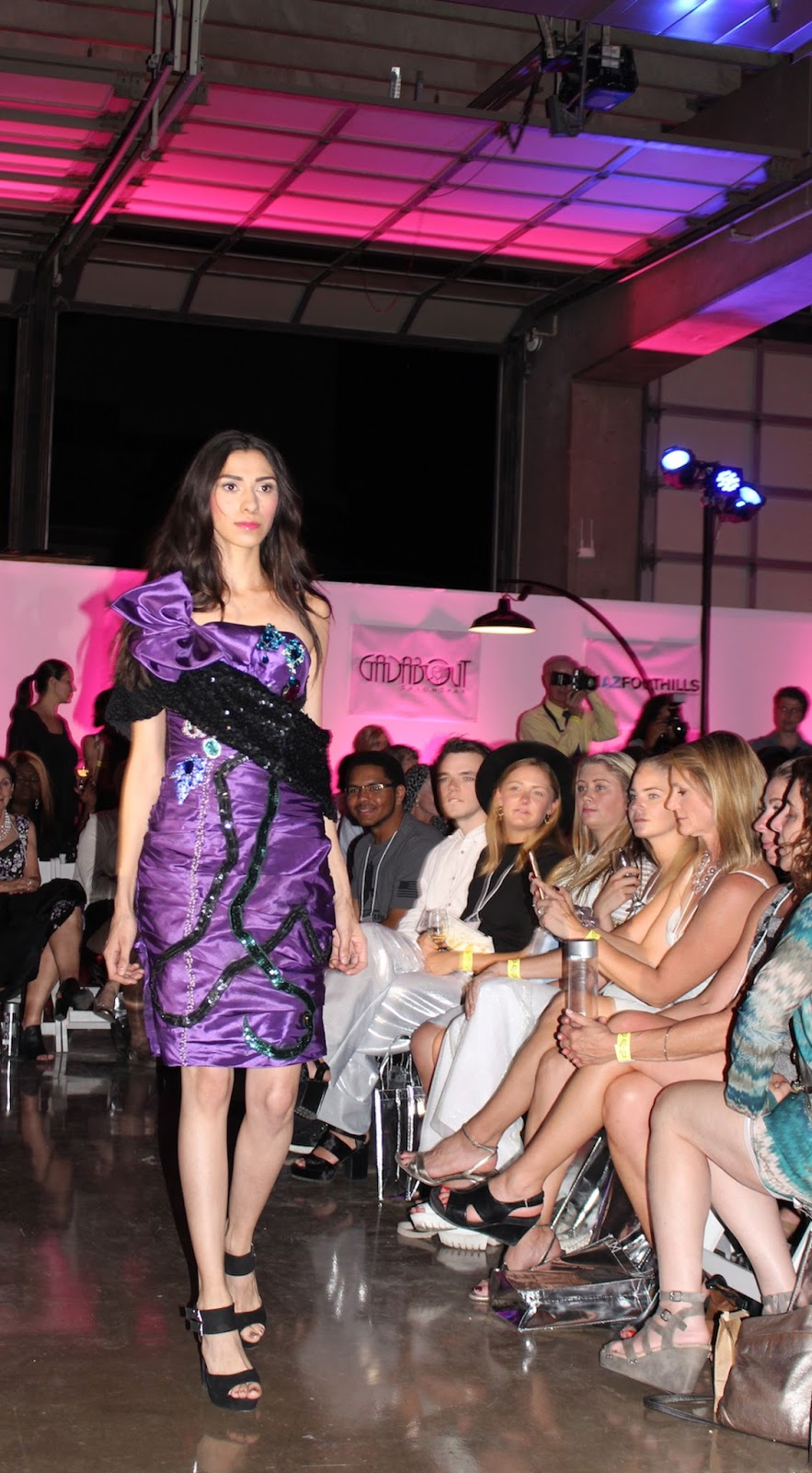 This mode is walking down the runway in a purple bejeweled dress with black detailing.