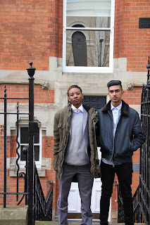 Two work experience students Haidar and Tinashe standing together outside the Outreach department office