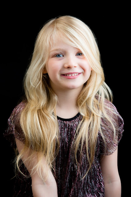 A young girl with long blonde hair smiling at the camera