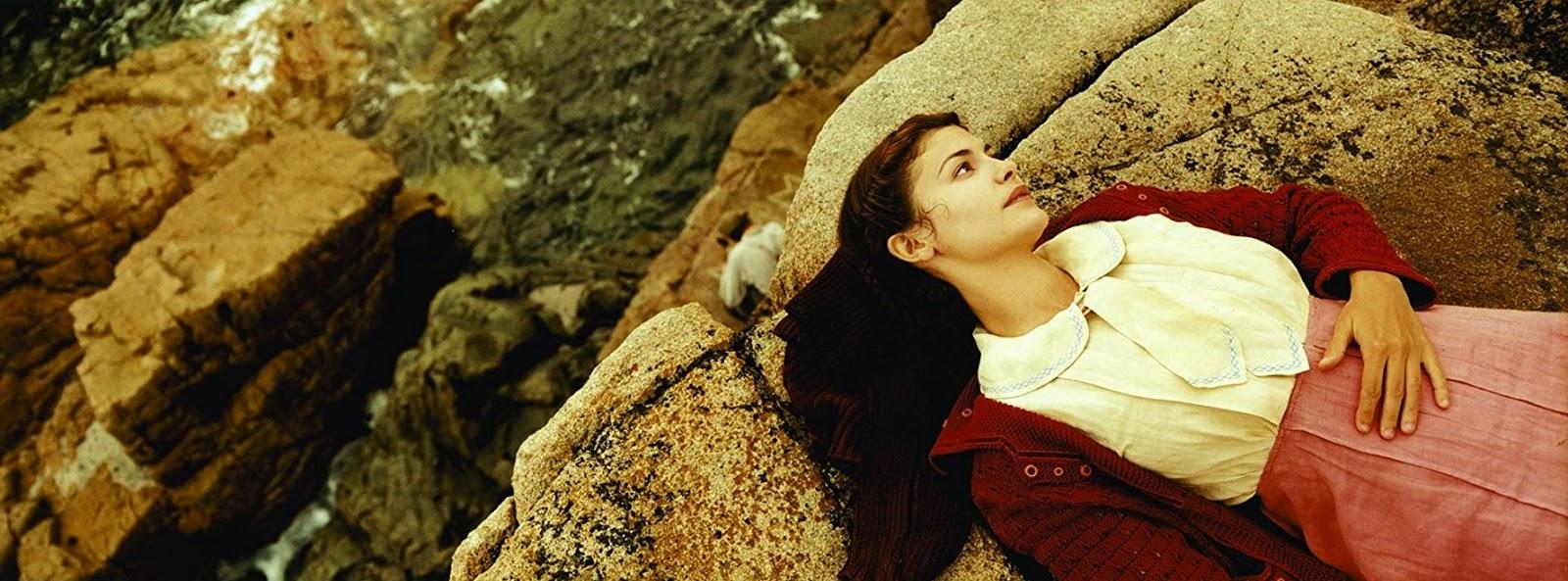 La protagoniste allongée sur une plage de rochers