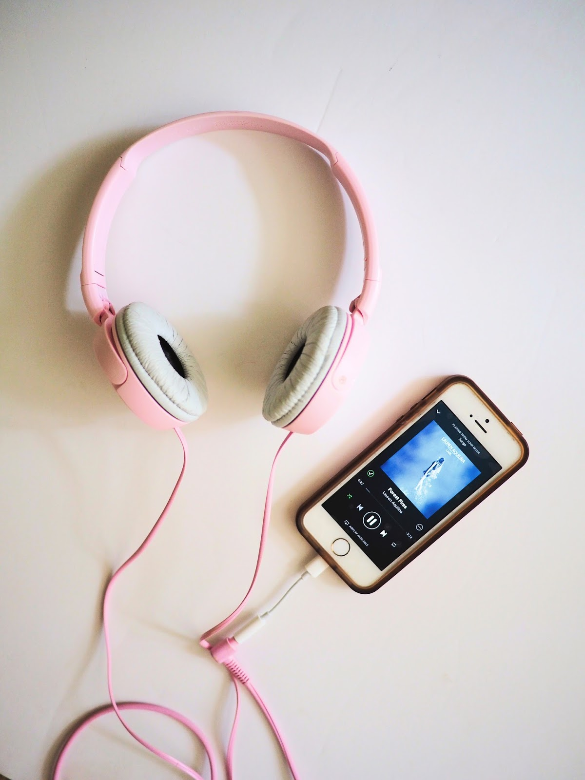 pink headphones and phone playing music