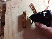Apply hot glue along the birch strip of the mount