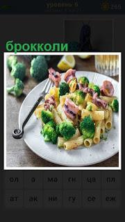 Тарелка с едой в которой находится брокколи и вилка