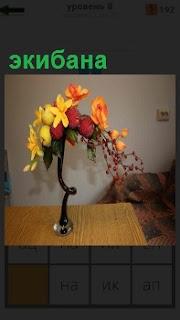 На столе стоит экибана, выполнена в виде вазы с цветком внутри и ягодами