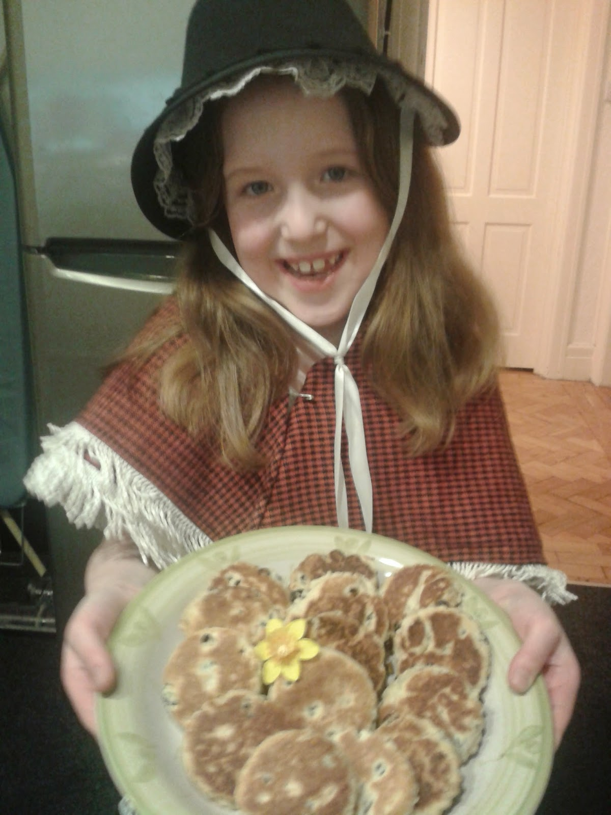 Welsh cakes recipe - Caitlin in Welsh Lady costume holding a plate of Welsh cakes
