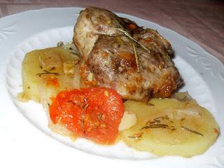 Pierna de cordero asada con patatas y tomate.