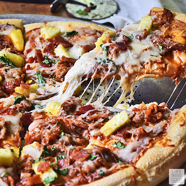 BBQ Pulled Pork Pizza - pulling a slice of pizza with cheese stretching