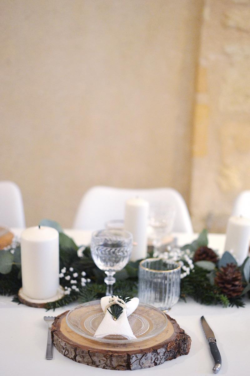 rondin de bois, assiette en verre maisons du monde, serviette blanche et branche de sapin, chaise maisons du monde