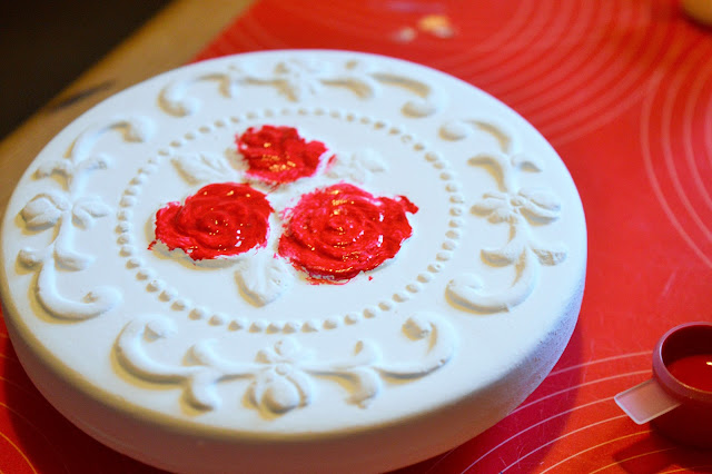 White jewellery box lid with painted red roses.