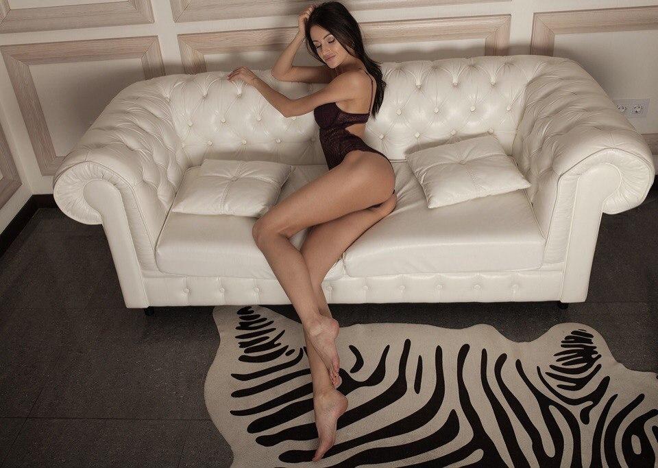 Sexy woman lying black leather sofa photos
