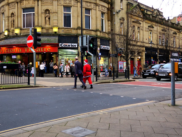 Tall man crosses road, hand in hand with Father Christmas, when pedestrian light is green