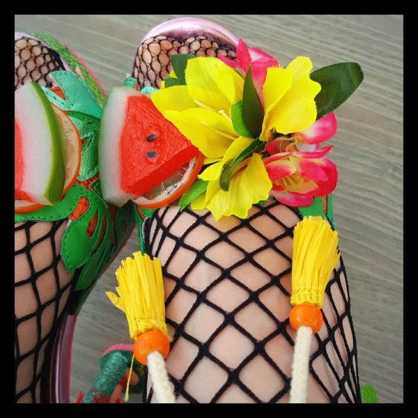 close up of plastic fruit and artificial flowers across toe of shoe, on foot with fishnet tights