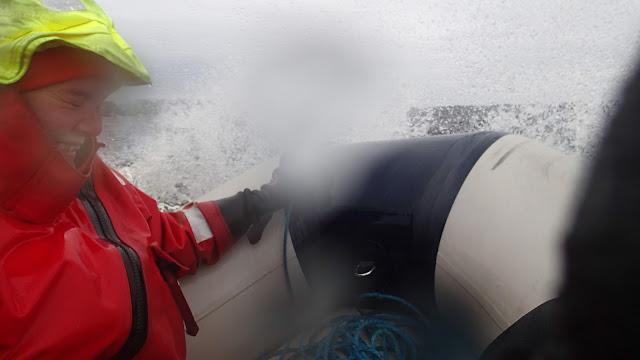 Vesi pärskyy kumiveneeseen ja pelastautumispukuun pukeutuneen henkilön päälle