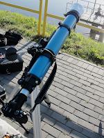 Wspomniana wyżej opcja lustrzanki w ognisku głównym teleskopu. W tym wypadku tuba optyczna refraktora Sky Watcher 90/910 posłużyła za teleobiektyw z ekwiwalentem 1820 mm ogniskowej - zdjęcie setupu wykonałem podczas tranzytu Wenus z 6 czerwca 2012 roku. Takie połączenie umożliwiało wykonanie ostrych fotografii, na których tarcze Słońca i Wenus mogły być widoczne w dużej skali przy zachowaniu wysokiej rozdzielczości zdjęć, ale jako, że przejście Wenus na tle tarczy słonecznej miało miejsce przy wschodzie Słońca na niskich elewacjach (tak jak będzie to z nadchodzącym zaćmieniem Księżyca) to jedna długość ogniskowej, którą mogłem wykonywać fotografie zjawiska była jednocześnie kulą u nogi. Obraz momentami falował jak nad ogniskiem, a ostre wychodziło jedno zdjęcie na kilkanaście wykonanych seryjnie. Przy zawieszeniu obiektu nisko nad horyzontem i wahaniach seeingu, bezpieczniej mieć możliwość stosowania szerokiej gamy ogniskowych zamiast wyłącznie jednej długości, bo w takich sytuacjach stan atmosfery często mocno obniża granicę użytecznych ogniskowych.