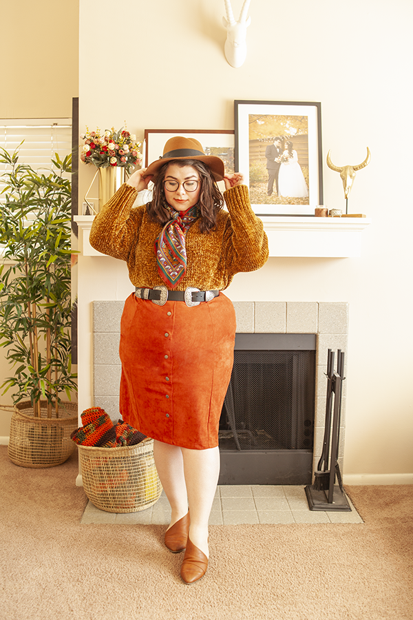 An outfit consisting of a camel brown wide brim fedora, a brick red maroon print neck scarf, a mustard chenile sweater, a burnt orange button down midi skirt, and brown d'orsay flats.