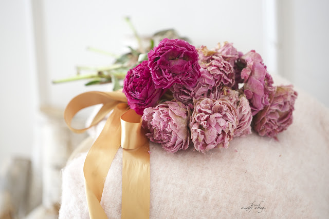 Dried peonies on a blush blanket with ribbon