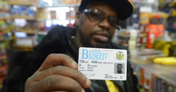 Man holding up EBT/ food stamps card