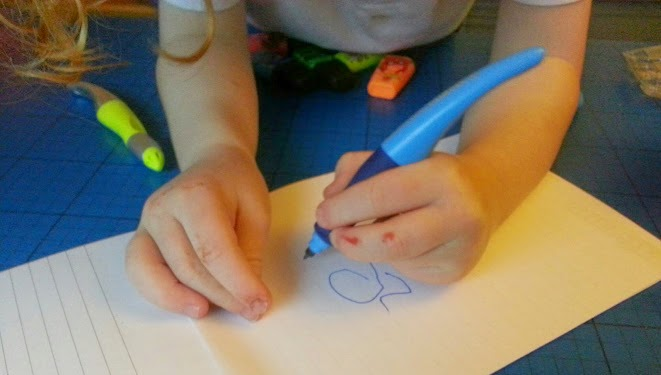 4 year old left handed boy writing with shaped pen