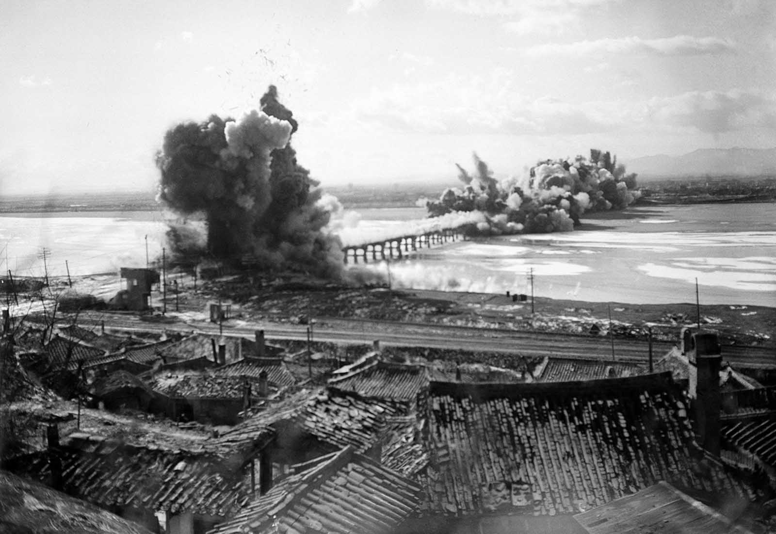 High explosives rip through several spans of a railroad bridge outside Hamhung as United Nations forces blow up the bridge as part of their withdrawal to prevent its being used by Chinese Communists on December 19, 1950.