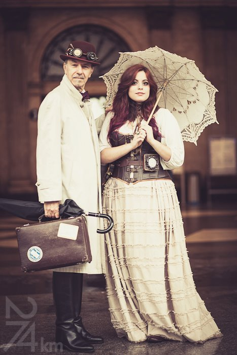 Steampunk man and woman in victorian clothing. Parasol, corset, skirt, hat and goggles.