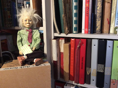 puppet Johnny Dwyer by Corina Duyn sitting on a box in front of bookshelf