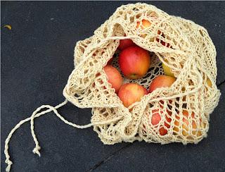 A drawstring bag mesh bag left partially open.  The bag has apples inside.