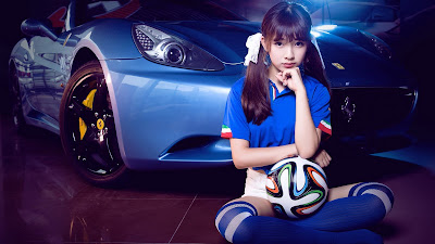 Linda chica con coletas y balón de fútbol con coche de fondo