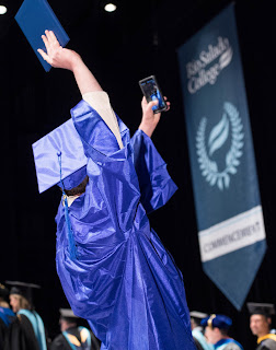 Image of dual enrollment student in cap and gown taking a selfie at graduation