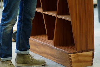 Image of a man's legs wearing jeans and standing beside a cabinet.