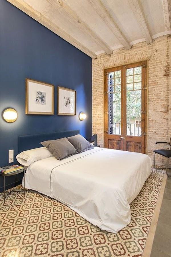 Dormitorio con pared de cabecero azul petróleo, lagrillos vistos y suelos hidraúlicos