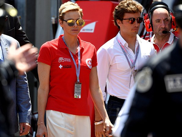 Prince Albert and Princess Charlene at Formula 1 Grand Prix. Princess Charlene wearing the T Shirt of the red cross of Monaco